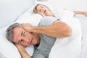 Man covering ears next to snoring woman