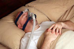 man sleeping wearing cpap mask