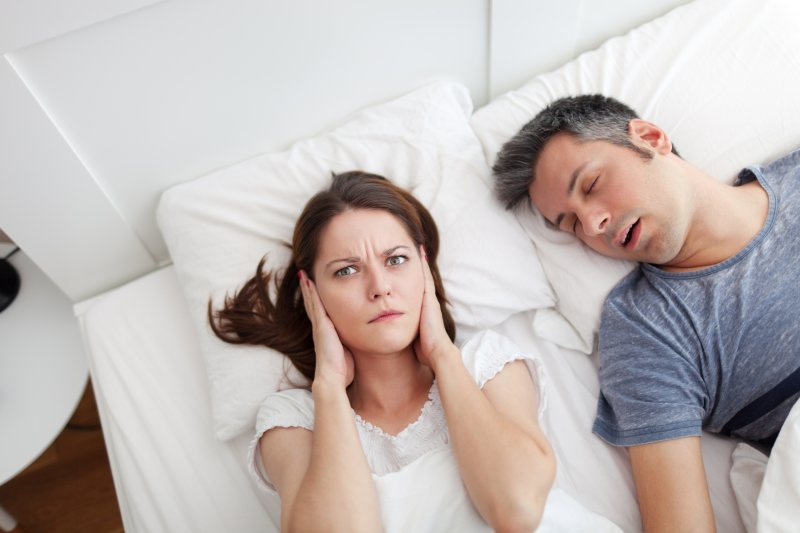 woman upset with man snoring
