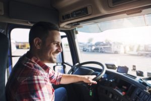 Inside shot of man in plaid smiling while driving a truck
